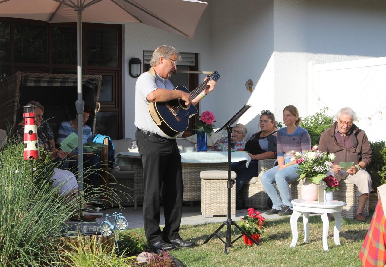 Gemeinde trifft sich im Garten des Pfarrers