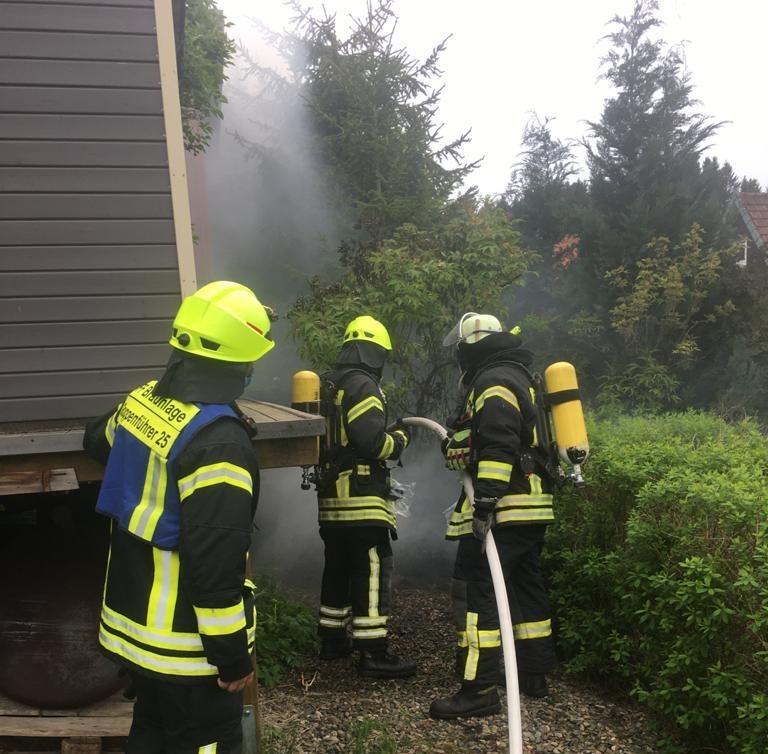 Komposthaufen brennt neben Gartenlaube